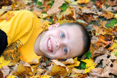 Beaming an Autumn Smile. Young child face is beaming as he enjoys the Autumn leaves he is laying on.  Smile continues into his gleaming eyes Stock Photos