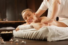 Beaming blonde woman being in great mood during massage session. Experienced massage master. Beaming blonde women being in great mood during massage session royalty free stock photography
