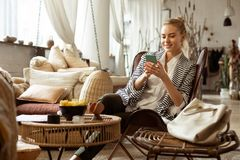 Beaming blonde woman resting in comfortable spacious armchair. Leisure zone. Beaming blonde woman resting in comfortable spacious armchair and chatting on a stock images