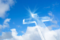 Beaming bright white cross in heaven. Christian cross over a beautiful sky background, for holiday, Christmas, Easter and religion designs stock photography