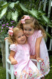 Beaming Bundles of Joy. Beautiful young girls glow beauty and joy. Both are dressed identical with light pink dresses ande hairbows. One is sitting in a white stock images
