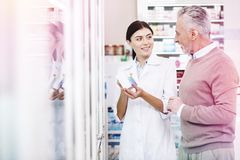 Beaming consultant explaining effect of the medicines. Explaining effect. Beaming consultant explaining to a curious customer negative and positive effect of the royalty free stock photography