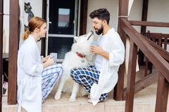 Beaming couple having fun with their white dog in the morning Royalty Free Stock Photo