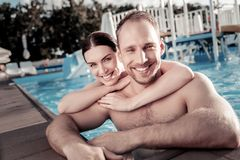 Beaming couple relaxing and swimming in pool royalty free stock photos
