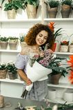 Beaming creative florist showing amazing bouquet for her client royalty free stock photos