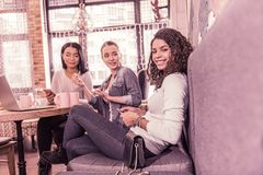 Beaming curly dark-haired woman sitting on grey sofa in cafeteria with her friends. Grey sofa. Beaming curly dark-haired women sitting on grey sofa in cafeteria royalty free stock images
