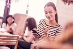 Beaming dark-haired woman having nice idea while typing message for her friend. Have idea. Beaming dark-haired women wearing striped shirt having nice idea while stock photo