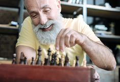 Beaming elderly gentleman playing chess. Cannot keep my emotions inside. Selective focus on a face of an extremely happy senior man smiling with excitement while royalty free stock photos