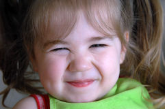Beaming Face. Of little girl, shows her teasing personality.  Her eyes are scrunched and her lips are grinning Stock Image