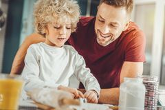 Beaming father hugging his cute curly boy rolling out pastry royalty free stock images