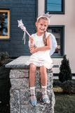 Cute beaming girl wearing fairy wings and holding magic wand having fun royalty free stock photography