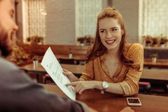 Beaming girl pointing at the menu sitting at bar counter. A women with a menu. Beaming smiling glowing pretty red-haired stylish elegant girl pointing at the stock images