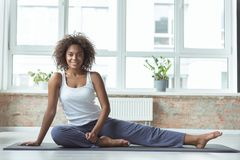 Beaming girl practicing iyoga n apartment Royalty Free Stock Image