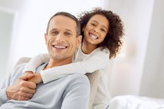 Content girl hugging her daddy. Beaming. Good-looking alert dark-haired father sitting in the arm-chair and smiling and his daughter standing behind him Royalty Free Stock Image