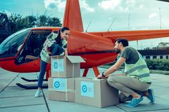 Beaming good-looking guys taking out clothes from boxes with aid. Checking things. Beaming good-looking guys taking out clothes from boxes with aid while having royalty free stock photography