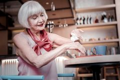 Beaming good-looking senior woman resting in a cafe and treating stock photos