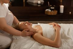 Beaming good-looking visitor of SPA center enjoying experienced movements. Professional skilled masseuse. Beaming good-looking visitor of SPA center enjoying stock images