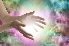 Beaming healing energy. Outstretched female healing hands with white light between and a vibrant multicolored flowing energy field background stock photo