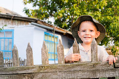 Beaming little boy in a summer. Beaming happy little boy in a sunhat standing holding on to the slats of a wooden picket fence enjoying the summer sunshine Stock Photography