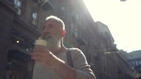 Beaming man enjoying his coffee while walking stock video