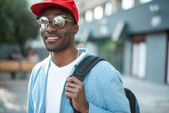 Beaming man holding luggage in arms. Portrait of cheerful male tourist carrying bag while walking around city Stock Photo