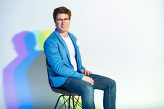 Beaming man sitting on chair. Portrait of happy male locating on seat while looking at camera. Multicolored shadow. Cheerfulness concept Stock Images