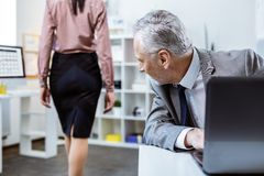 Inappropriate senior worker actively turning around while female colleague. Beaming old man. Inappropriate senior worker actively turning around while female stock images
