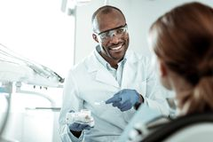 Beaming positive dentist wearing white uniform and protective glasses stock images