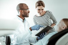 Beaming positive mother looking on the screen of the tablet. Dentist using tablet. Beaming positive mother looking on the screen of the tablet examining royalty free stock photography