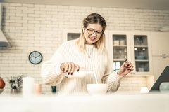 Beaming pretty lady pouring milk from glass bottle stock image