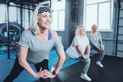 Beaming senior lady taking group training at gym. Say no to arthritis pain. Selective focus on a joyful women smiling while lunging with a group of elderly Stock Image