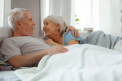 Beaming silver-haired bearded man embracing his smiling aged short-haired spouse. Lovingly embrace wife. Beaming nice-looking attractive silver-haired bearded stock photography