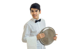 A beaming wonderful waiter in a white shirt holding a tray. Of  on white background Stock Photos