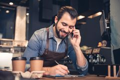 Beaming worker noting and telling on mobile. Low angle portrait of cheerful bearded barista writing information while speaking on mobile in modern cafe. Job Stock Photos