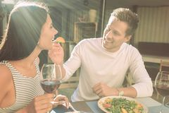 Beaming young man in white shirt lovely looking on his girlfriend stock photography