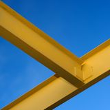 Beams. Yellow painted steel I beams against a blue sky stock photography