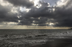 Beams through clouds at the sea Royalty Free Stock Photo