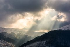 Beams of light over the mountains. Gorgeous scenery on a cloudy day in winter stock image