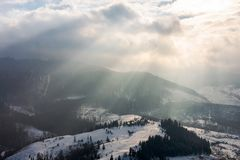 Beams of light on winter morning. Beautiful countryside with snowy hill royalty free stock photo