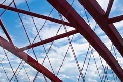 Beams of a red arched bridge close-up against a blue sky. texture of the lattice of the parts of the steel bridge. cropped stock photo