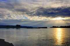 Beams of the rising sun pass through the clouds and reflect on the river water Royalty Free Stock Image
