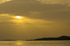 Beams of yellow light with refletions on a water surface before sunset, Sithonia Royalty Free Stock Image
