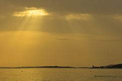 Beams of yellow light with refletions on a water surface before sunset, Sithonia Royalty Free Stock Photography