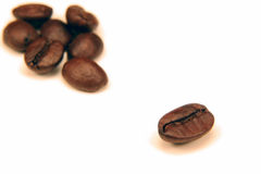Bean Alone. One coffee bean seperated from the a group of them on white stock photo