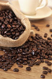 Bean coffee. Coffee beans in a bag on a wooden table. In the background the white cup Royalty Free Stock Image