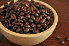 Bean coffee. Coffee beans in a wooden bowl on a wooden table Stock Image