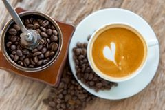 Bean coffee with latte art or cappuccino on wooden table Stock Image
