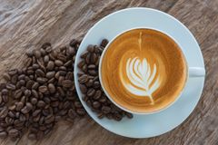 Bean coffee with latte art or cappuccino on wooden table Royalty Free Stock Photography