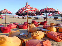 Bean cushions and umbrellas on beach Stock Images