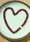 Bean Missing You A. Red beans arranged in a heart shape with one missing placed on a white plate Royalty Free Stock Image